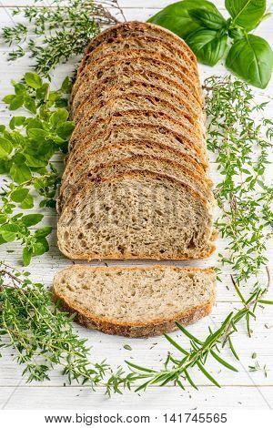 Provence herbs sourdough bread on a white table board