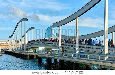 Barcelona Spain - April 3 2016: Crowd of people walking across the swing bridge on the Rambla de Mar in Barcelona city. The Ramla del Mar is a main tourist attraction in Barcelona. Spain