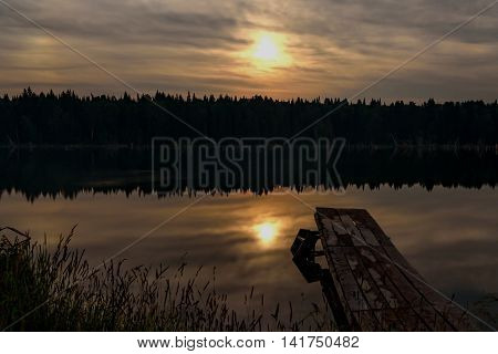 Night landscape with the moon clouds forest reflections and moonlight on the smooth water of the lake