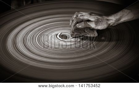 The hand of unrecognizable person draws by sponge and clay on the potter's wheel. Filter sepia selective focus.