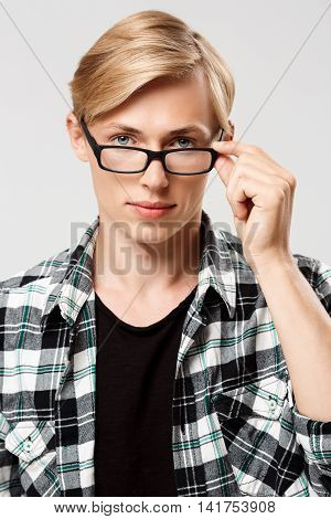 Close up portrait of handsome blond young man in glasses wearing casual plaid shirt looking at camera isolated on grey background