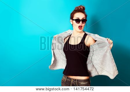 Hipster Girl in Sunglasses and Jeans Shirt Posing at Turquoise Background. Trendy Hairstyle with Hair in a Bun. Street Style Fashion Outfit. Toned Photo with Copy Space.