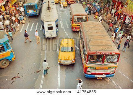 KOLKATA, INDIA - JAN 20, 2013: Transport motion on street with yellow Ambassador taxi tram and public buses at rush hour on January 20, 2013. Kolkata has a density of 814.80 vehicles per km road length