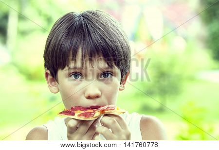 boy eating pizza on the nature happy