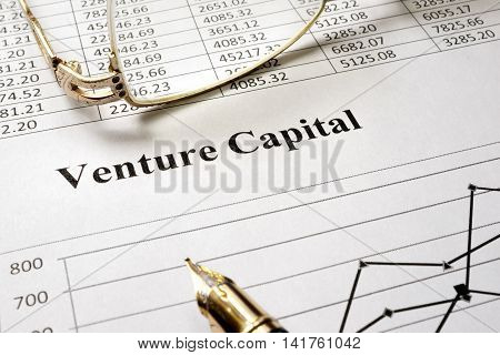 Sign venture capital on a paper and glasses.