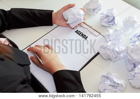 Hands of woman crumple sheets of Agenda for presentation at the desk mistake agenda.