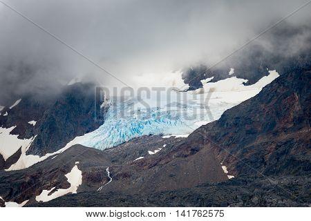 Large blue iceberg draped in fog on a mountain peak near Skagway AK