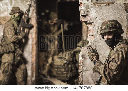 Closer shot of a soldier standing close to the wall in helmet and showing the way with other soldiers at the background