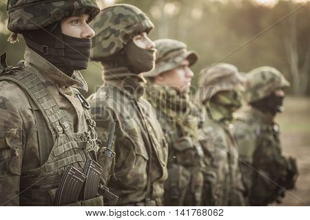 Five soldiers standing in a rank in camouflage clothes and helmets
