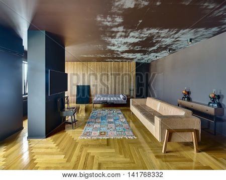 Room in a modern style with various walls and parquet with colorful carpet on the floor. There is column with TV, vinyl player, sofas, chairs, picture, stand with candlestick, doors, rack with lamps.