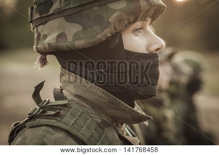 Close shot of young soldier face in camo helmet with other soldiers at the background