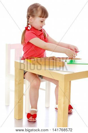 Cute little girl sitting at a table in a Montessori kindergarten. The girl works with Montessori material-Isolated on white background