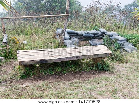 Old bamboo bench in front of the old bunker in the deactivate base which located on the high mountain.