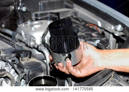 mechanic in the hand, remove car oil filter