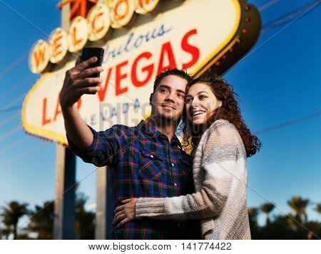 romantic selfie in front of lit up las vegas sign at early evening