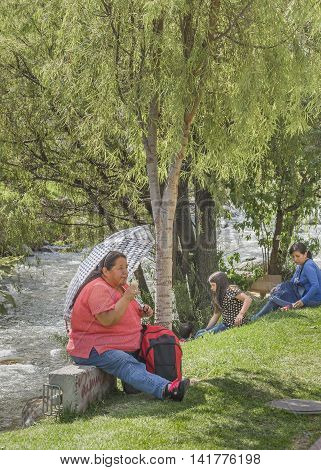 CUENCA, ECUADOR, NOVEMBER - 2015 - Group of people enjoying the day at park in front of river in Cuenca Ecuador