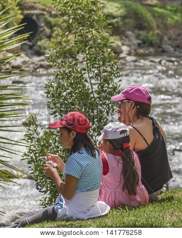 CUENCA, ECUADOR, NOVEMBER - 2015 - Woman with his children enjoying the day at park in front of river in Cuenca Ecuador
