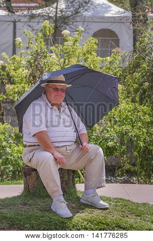 CUENCA, ECUADOR, NOVEMBER - 2015 - Adult fan man with umbrella sitting enjoying the day at park in front of river in Cuenca Ecuador