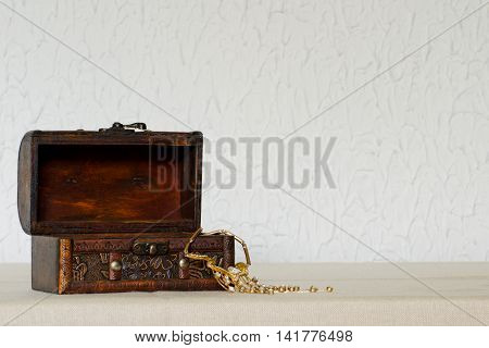 Open wooden vintage jewelry box with a necklace on a white background