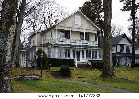 WEQUETONSING, MICHIGAN / UNITED STATES - DECEMBER 22, 2015: An elegant home with an enclosed front porch and a balcony on Beach Drive in Wequetonsing.