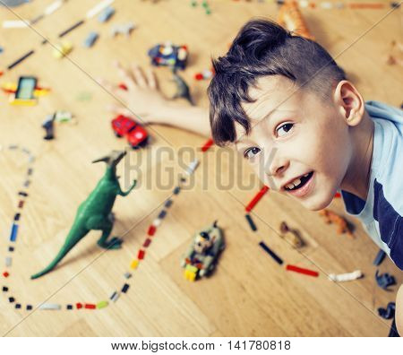 little cute preschooler boy playing lego toys at home happy smiling, lifestyle children concept, world map with pieces poster