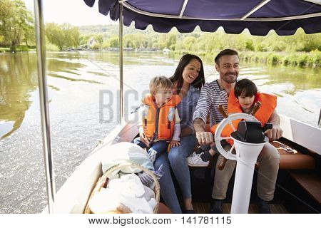 Family Enjoying Day Out In Boat On River Together