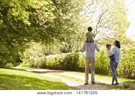 Rear View Of Family Going For Walk In Summer Countryside