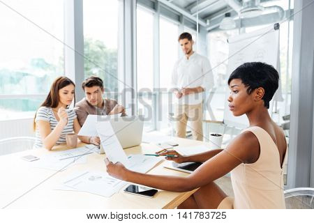 Four confident young businessmen making business plan using laptop and flipchart in office