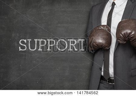 Support on blackboard with businessman wearing boxing gloves