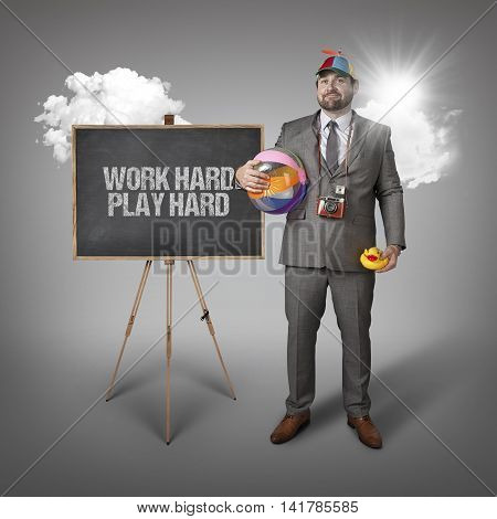 Work hard play hard text with holiday gear businessman and blackboard with text