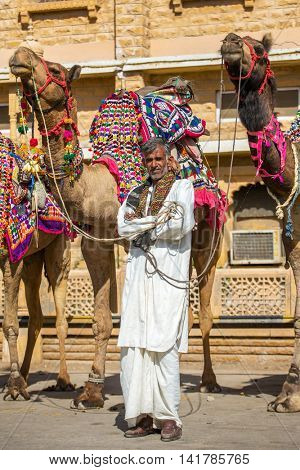 Jaisalmer, India - March 3, 2016: Unidentified rajasthani man with camels waiting for tourists in Jaisalmer, India.