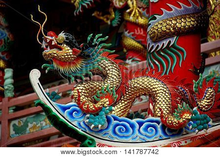 Bang Saen Thailand - January 7 2010: A colourful dragon sits atop a flying eave roof at the Dao De Tian Lin Chinese  temple