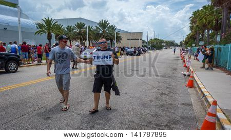 Daytona Beach, FL - August 3, 2016: Two Donald Trump supporters walk down the street at a Republican rally holding a Donald Trump sign.  Other supporters in the background wait in line to get in the Arena to hear Donald Trump speak.