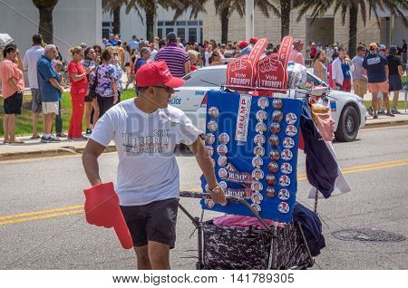 Daytona Beach, FL - August 3, 2016: A vendor pulls his cart of Donald Trump souvenirs at a rally in Daytona Beach, FL.  Supporters stand in line to get into the arena to hear Donald Trump speak.