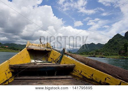 Boat trip on the Son river to the Phong Nha Cave in Phong Nha-Kẻ Bàng National Park Central Vietnam. View of the prow and mountains in the.turquoise water. Sunny summer picture with small clouds.