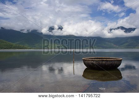 Traditional Vietnamese basket boat in the calm bayou. Steady water with reflection. Clouds and blue skyline mountains. Ga Lang co near Hai Van pass central Vietnam.