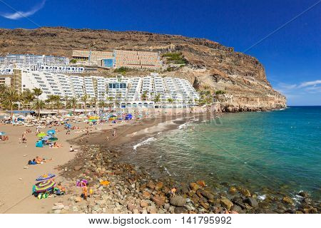 TAURITO, GRAN CANARIA, SPAIN - APRIL 24, 2016: Tourists on sun holidays at the Taurito beach, Gran Canaria. Taurito is very popular tourist destination
