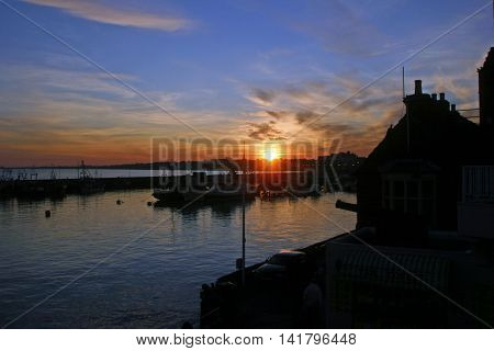 Sunset from Bridlington harbour in East Yorkshire with still water and fishing boats.