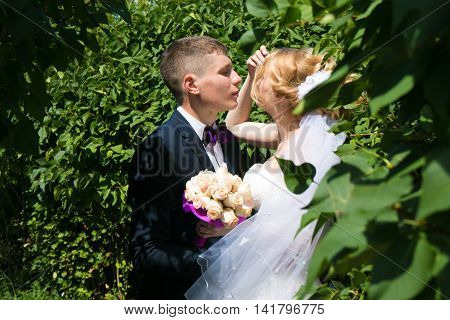 groom and bride kissing in the park