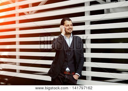 Handsome man talking on mobile phone and smiling, laughing wealthy man talking on mobile phone, young male having a phone talk