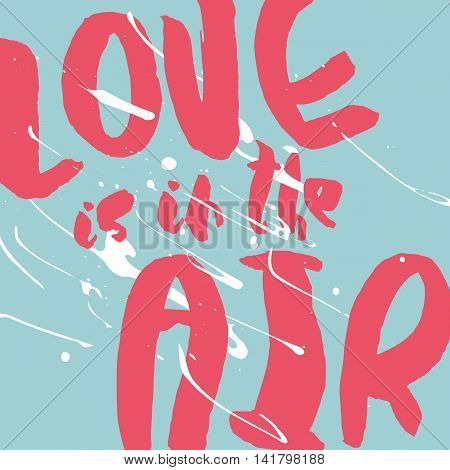 Decorative romantic poster with handlettering. Love is in the Air handwritten phrase. Pink lettering on blue background with white splashes. Design element for wedding or valentines day