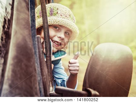 The little girl looks out the car window and shows a gesture okay.