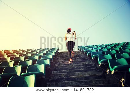young fitness woman runner athlete running up on stairs.