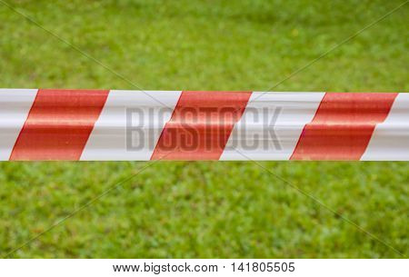 Red and white warning tape on green grass background in summer