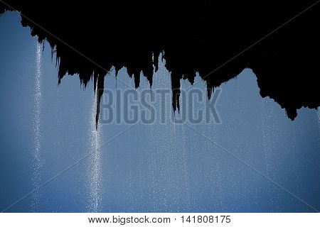 Silhouette of water falling off moss with a blue sky
