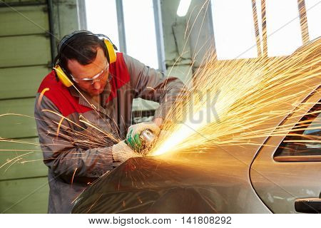 collision repairs service. mechanic grinding car body by grinder poster
