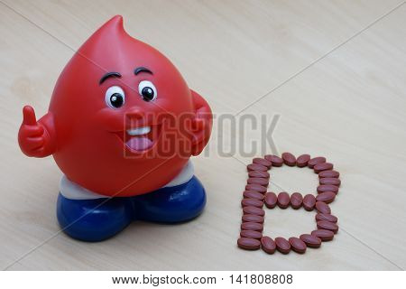 Ferrous Fumarate 200 mg with Vitamins for blood donor type B after donating blood on wood background. poster