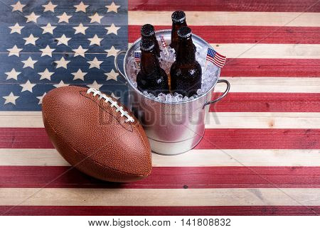 Top view of American football and bucket of ice cold beer on rustic wooden boards with painted USA Flag.
