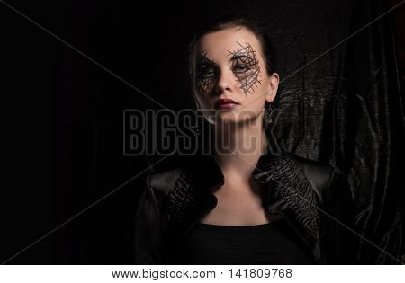 Young beautiful girl with make-up for Halloween body art on a woman's face mystical makeup