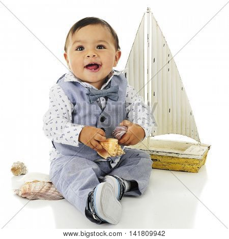 An adorable, dressed up baby boy delightedly playing with sea shells with his toy sailboat behind him.  On a white background.